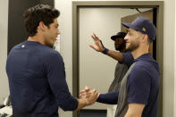 Milwaukee Brewers' Christian Yelich, left, greets teammate Ryan Braun after the Brewers announced Yelich's multi-year contract extension at the teams' spring training facility Friday, March 6, 2020, in Phoenix. (AP Photo/Matt York)