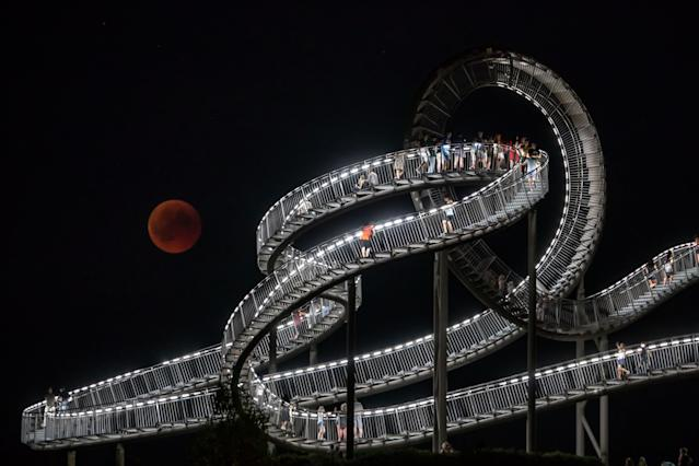 "<p>The full moon can be seen behind the landmark ""Tiger and Turtle"" sculpture and walkway during a ""blood moon"" eclipse over Duisburg, western Germany, on July 27, 2018. (Photo: Christoph Reichwein/ dpa /AFP/Getty Images) </p>"
