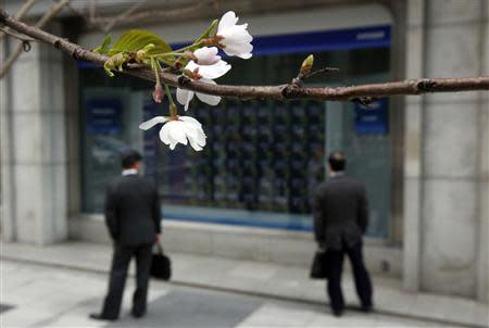 Two businessmen look at an electronic stock quotation board, as cherry blossoms bloom, outside a brokerage in Tokyo April 9, 2014. REUTERS/Issei Kato