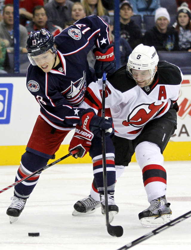 Columbus Blue Jackets' Cam Atkinson, left, works for the puck against New Jersey Devils' Andy Greene during the second period of an NHL hockey game in Columbus, Ohio, Tuesday, Oct. 22, 2013. (AP Photo/Paul Vernon)