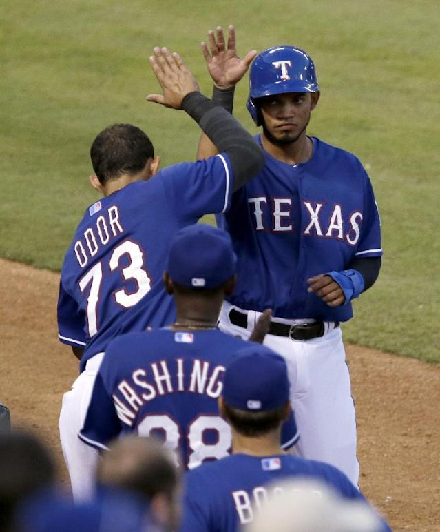 Texas Rangers' Rougned Odor (73) and Ron Washington (38) greet Luis Sardinas, top right, at the entrance to the dugout after Sardinas scored on a Shin-Soo Choo double in the fifth inning of a baseball game, Friday, June 27, 2014, in Arlington, Texas. (AP Photo/Tony Gutierrez)