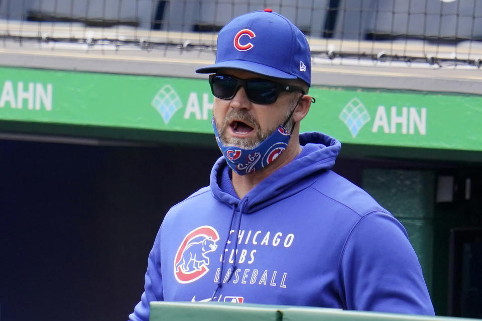 Chicago Cubs manager David Ross stands in the dugout during a baseball game against the Pittsburgh Pirates in Pittsburgh, Sunday, April 11, 2021. (AP Photo/Gene J. Puskar)