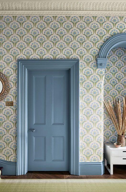"""<p>The soft cornflower blue of the Hencroft wallpaper by Little Greene is matched perfectly to the painted door and surrounding features. A particularly useful technique when the features in your home are a stark white or dark wood. </p><p>Pictured: <a href=""""https://www.littlegreene.com/hencroft-blue-primula"""" rel=""""nofollow noopener"""" target=""""_blank"""" data-ylk=""""slk:Hencroft Blue Primula Wallpaper at Little Greene"""" class=""""link rapid-noclick-resp"""">Hencroft Blue Primula Wallpaper at Little Greene</a></p>"""