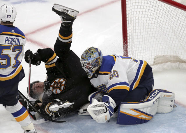 Boston Bruins' Charlie McAvoy, left, crashes to the ice in front of St. Louis Blues goaltender Jordan Binnington during the third period in Game 7 of the NHL hockey Stanley Cup Final, Wednesday, June 12, 2019, in Boston. (AP Photo/Charles Krupa)