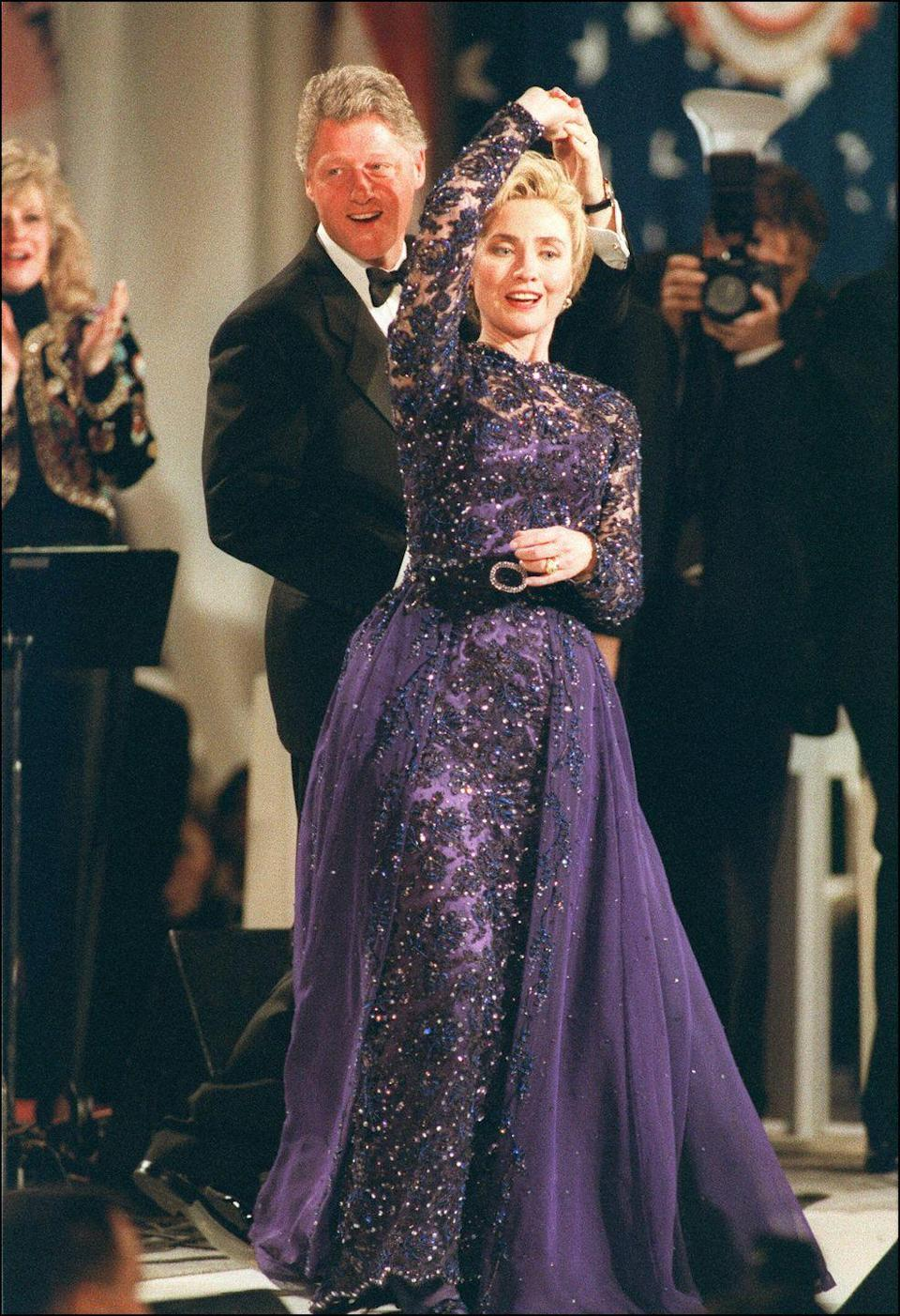 """<p>President Bill Clinton gives Hillary Clinton a twirl as they share the first dance at his inaugural ball. The First Lady looked lovely in a purple beaded ball gown with a tulle skirt that was <a href=""""https://www.si.edu/newsdesk/photos/hillary-clintons-inaugural-gown-1993"""" rel=""""nofollow noopener"""" target=""""_blank"""" data-ylk=""""slk:designed by Sarah Phillips"""" class=""""link rapid-noclick-resp"""">designed by Sarah Phillips</a>. </p>"""