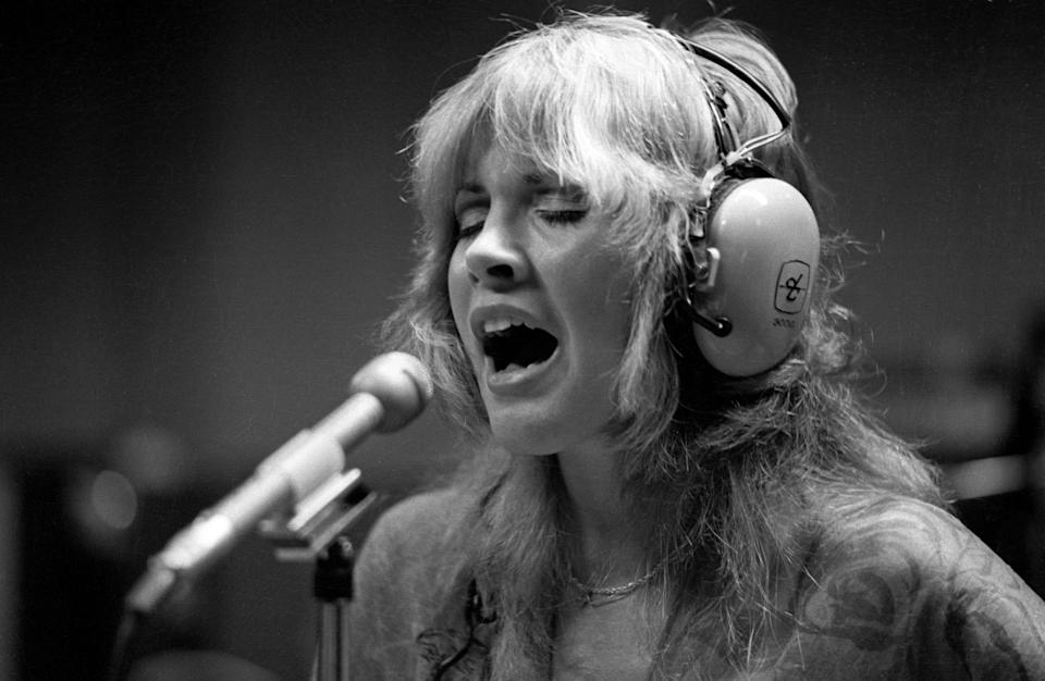 Photo of Stevie Nicks and FLEETWOOD MAC, Stevie Nicks singing in the recording studio, wearing headphones (Photo by Fin Costello/Redferns)