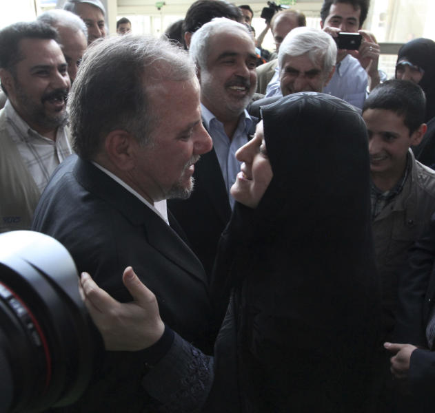 Iranian scientist, Mojtaba Atarodi, center left, who was in U.S. custody since late 2011 over allegations he bought high-tech equipment in violation of U.S. sanctions on Iran is welcomed by his wife, upon his arrival at the Imam Khomeini airport outside Tehran, Iran, Saturday, April 27, 2013. Atarodi arrived home via Oman, a Gulf state which has served as a mediator between Washington and Tehran before. (AP Photo/Vahid Salemi)