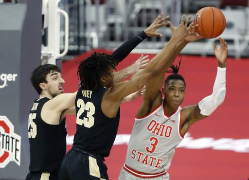 Ohio State guard Eugene Brown, right, passes against Purdue guard Ethan Morton, left, and guard Jaden Ivey during the first half of an NCAA college basketball game in Columbus, Ohio, Tuesday, Jan. 19, 2021. (AP Photo/Paul Vernon)