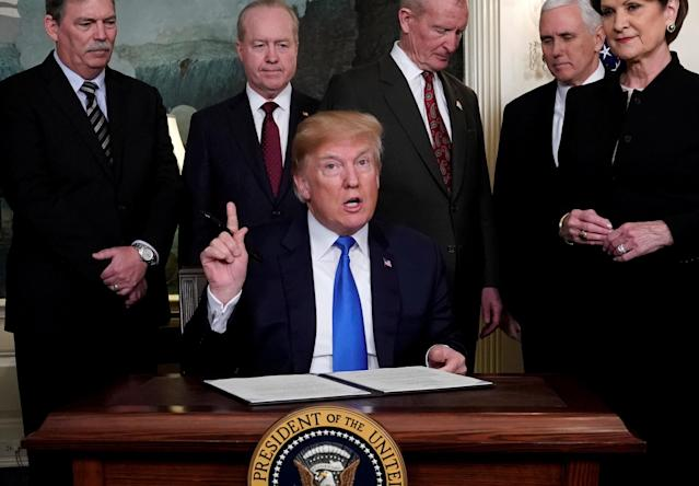 U.S. President Donald Trump, surrounded by business leaders and administration officials, prepares to sign a memorandum on intellectual property tariffs on high-tech goods from China, at the White House in Washington, U.S. March 22, 2018. REUTERS/Jonathan Ernst TPX IMAGES OF THE DAY