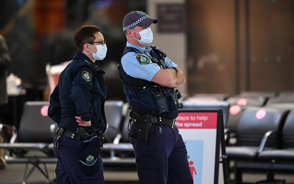 Police officers wear face masks as they watch passengers arrive from a Qantas flight at Sydney Airport on one of the last flights out of Melbourne to Sydney.