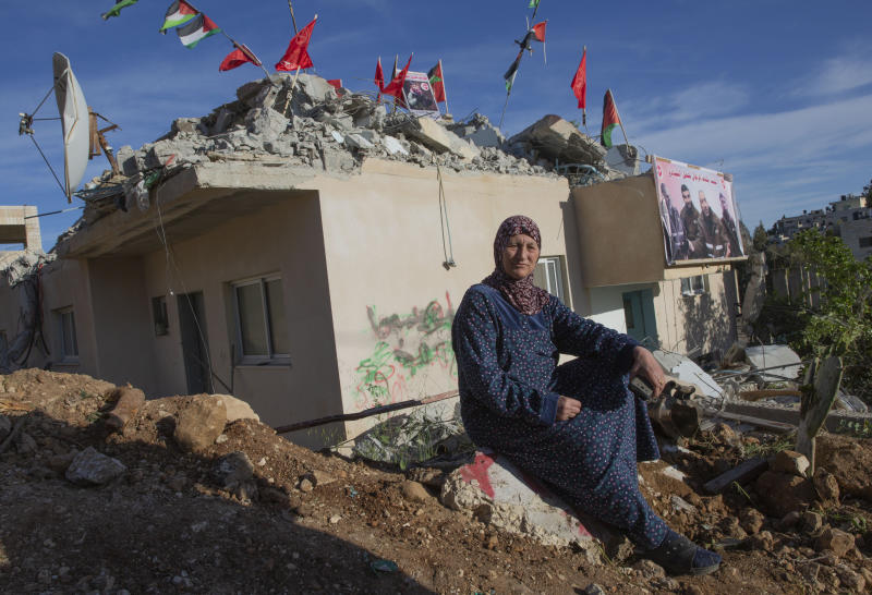 Palestinian Su'ad Barghuthi, sits on the rubble of her family building that was partly demolished by the Israeli army, in the West Bank village of Kobar, near Ramallah, Monday, May 11, 2020. The Israeli army demolished the top floor of the two story building that belongs to the Barghouti family during an overnight operation in the village. Israel says 22-year-old Qassem Barghouti carried out the attack in August, which killed 17-year-old Israeli Rina Shnerb and wounded her father and brother as they were hiking down to a spring in the West Bank near the settlement of Dolev. (AP Photo/Nasser Nasser)