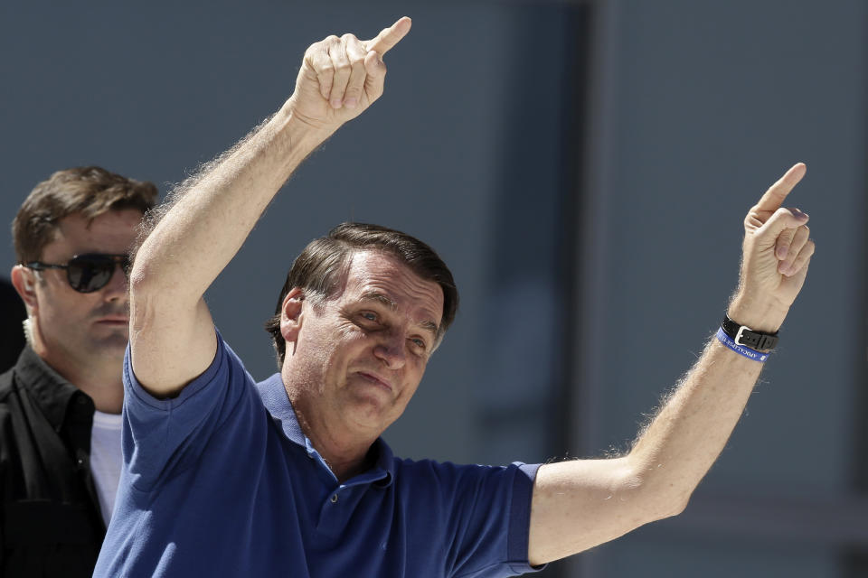 Brazil's President Jair Bolsonaro gestures to supporters during a protest against his former Minister of Justice Sergio Moro and the Supreme Court, in front of the Planalto presidential palace, in Brasilia, Brazil, Sunday, May 3, 2020. (AP Photo/Eraldo Peres)