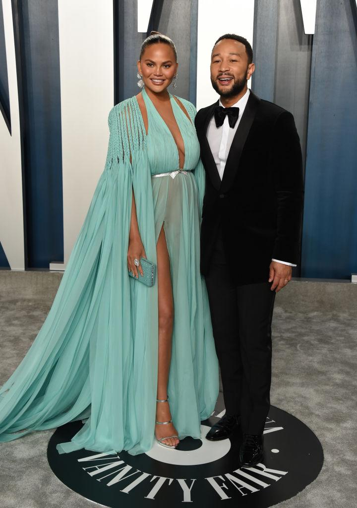 """Chrissy Teigen (pictured with husband John Legend) took to social media to share a """"thirst trap"""" video of herself in a swimsuit . (Photo by John Shearer/Getty Images)"""