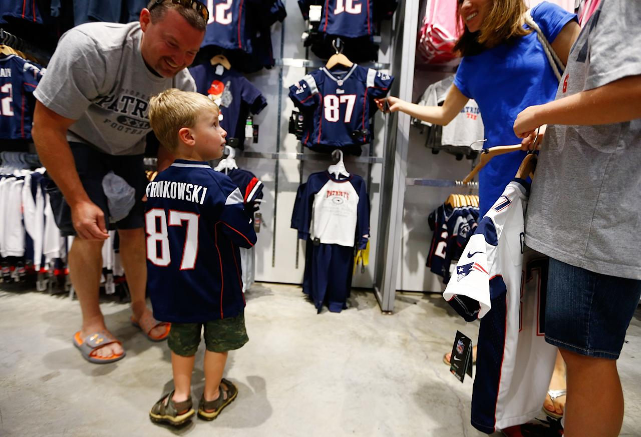 FOXBORO, MA - JULY 7: A young New England Patriots fans tries on a Rob Gronkowski jersey after exchanging their Aaron Hernandez jerseys during a free exchange at the pro shop at Gillette Stadium on July 7, 2013 in Foxboro, Massachusetts. (Photo by Jared Wickerham/Getty Images)