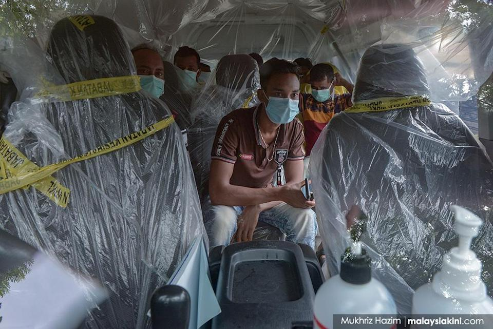 Foreign workers sit in a Health Ministry van covered with plastic as they make their way to the hospital for Covid-19 screening in Kampung Baru on Apr 14, 2020.