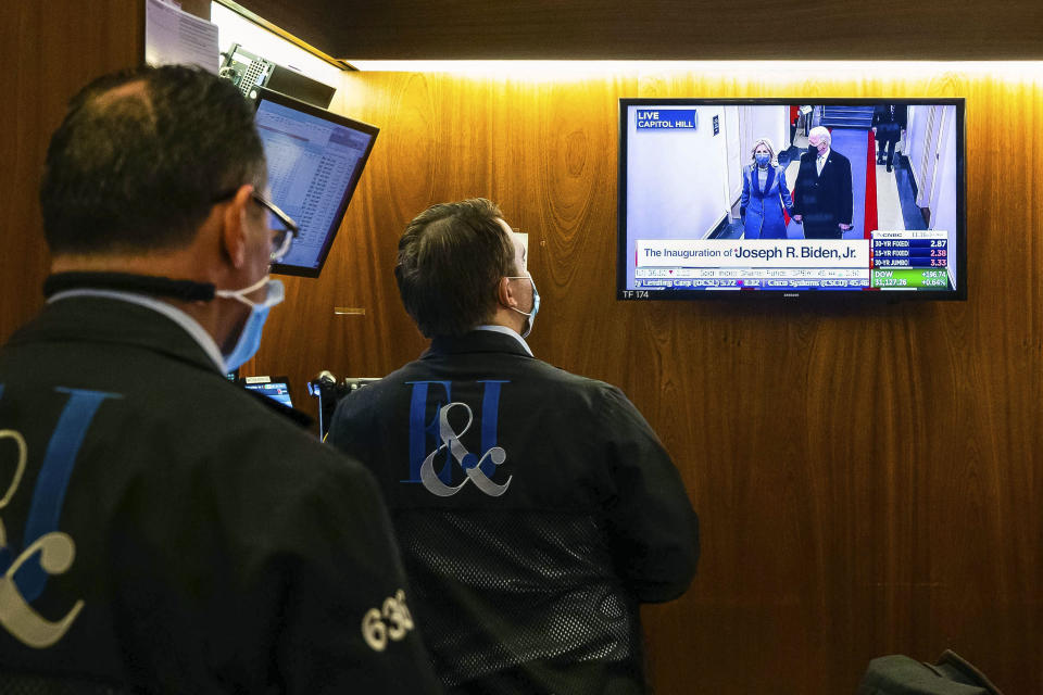 In this photo provided by the New York Stock Exchange, traders watch as the presidential inaugural plays on a screen, in a booth on the trading floor, Wednesday, Jan. 20, 2021. U.S. stocks are rallying to records Wednesday on encouraging earnings reports and continued optimism that new leadership in Washington will mean more support for the struggling economy. (Colin Ziemer/New York Stock Exchange via AP)