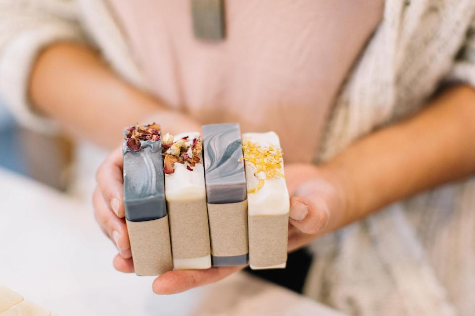 Someone holding four artisanal bars of soap together