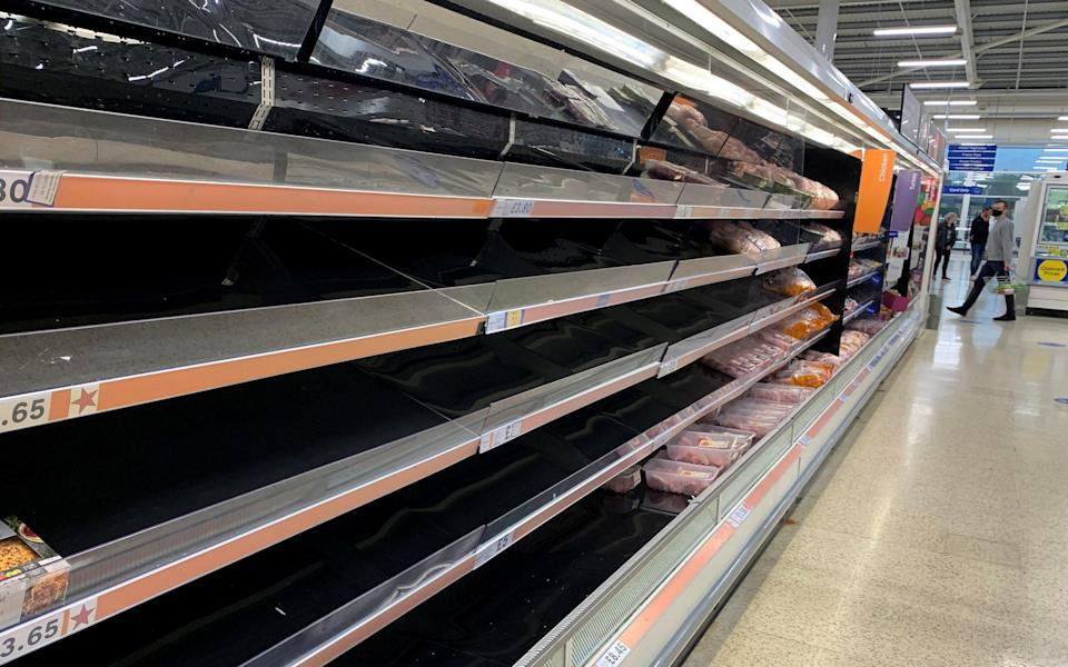 A shopper walks past empty shelves in the meat aisle of a supermarket in Manchester yesterday - Reuters