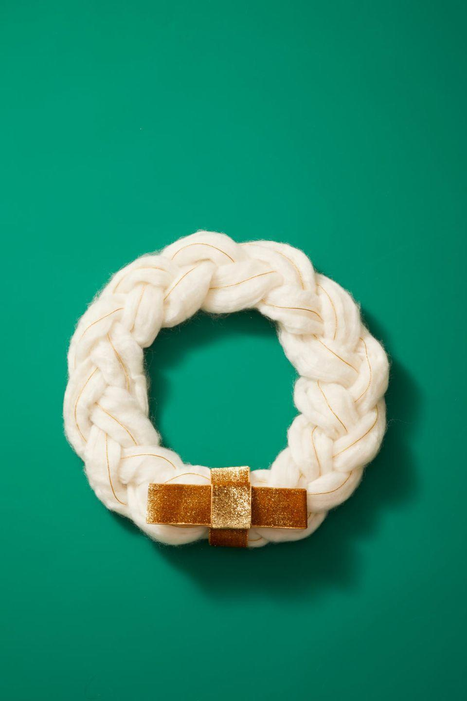 """<p>This craft is simple and sweet, and you can use up your extra yarn and ribbon while you make it. Just separate <a href=""""https://www.amazon.com/Bernat-Softee-Chunky-Gauge-Natural/dp/B007RL3ACK?tag=syn-yahoo-20&ascsubtag=%5Bartid%7C10055.g.2996%5Bsrc%7Cyahoo-us"""" rel=""""nofollow noopener"""" target=""""_blank"""" data-ylk=""""slk:the yarn"""" class=""""link rapid-noclick-resp"""">the yarn</a> into three equal segments, and then add a thin ribbon to each one. As you braid, make sure the ribbon stays in the center. Complete the braid by tucking the ends underneath the wreath, and secure them with a small amount of hot glue. Then, glue the braided yarn onto the <a href=""""https://www.amazon.com/Green-Wire-Wreath-Form-Diameter/dp/B01G465SB4?tag=syn-yahoo-20&ascsubtag=%5Bartid%7C10055.g.2996%5Bsrc%7Cyahoo-us"""" rel=""""nofollow noopener"""" target=""""_blank"""" data-ylk=""""slk:wreath form"""" class=""""link rapid-noclick-resp"""">wreath form</a>, and tie a bow around the bottom.</p>"""