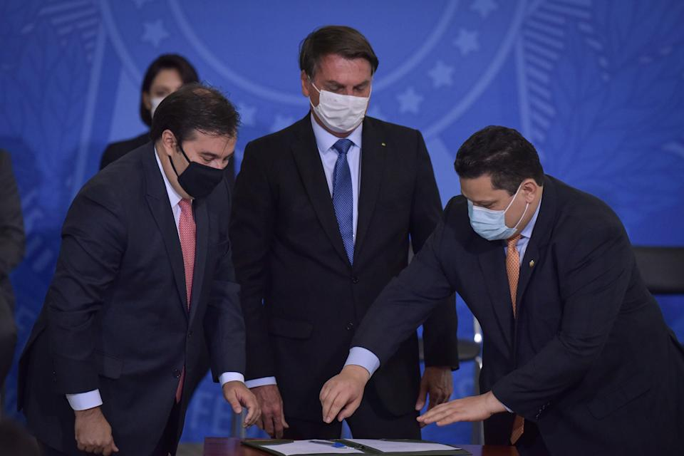 Next to Brazil's Lower House Speaker Rodrigo Maia (left) and the President of the Senate Davi Alcolumbre (right), Brazil's President Jair Bolsonaro reacts during the Emergency Aid Extension ceremony at the Planalto Palace in Brasília, Brazil, on June 30, 2020. The Emergency Aid is a financial benefit granted by the Federal Government to workers and unemployed people affected by the Coronavirus (COVID-19) pandemic. (Photo by Andre Borges/NurPhoto via Getty Images)