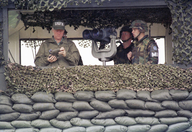 FILE - In this July 11, 1993, file photo, U.S. President Bill Clinton takes the lens caps off a pair of binoculars at Camp Casey from the Ouellette guard post in the Demilitarized Zone (DMZ), the tense military border between the two Koreas, in Panmunjom, South Korea. President Donald Trump is inviting North Korea's Kim Jong Un to shake hands during a visit to the demilitarized zone with South Korea. Trump is scheduled to visit South Korea later Saturday after meetings at the Group of 20 summit in Osaka, Japan. (AP Photo/Greg Gibson, File)
