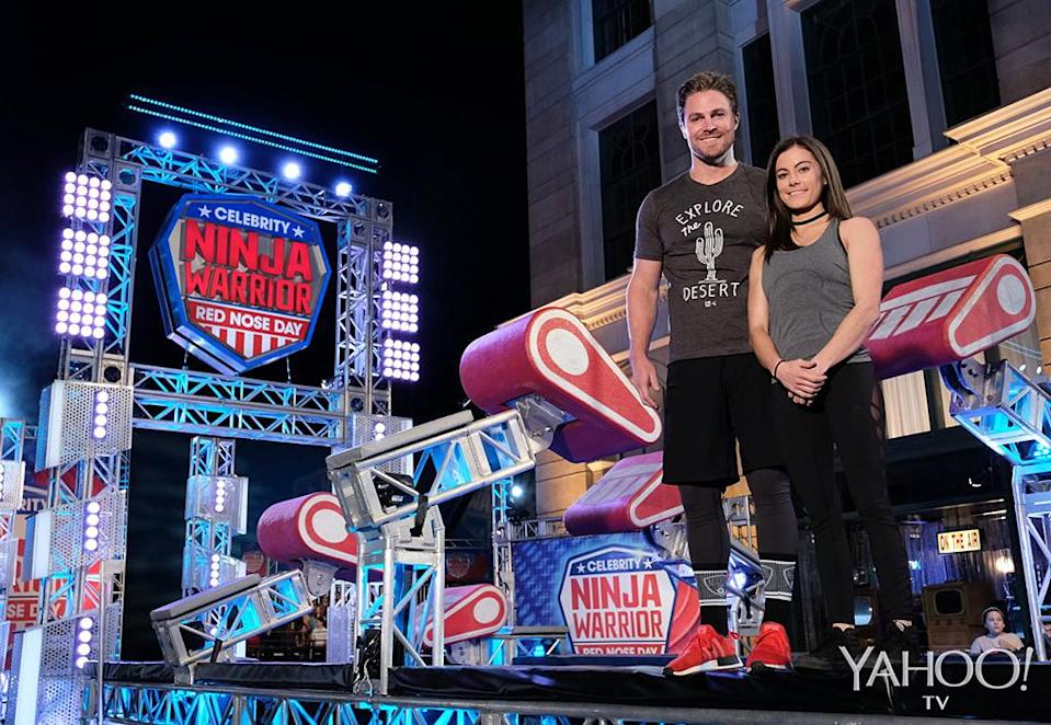 <p>Each celebrity is paired with an experienced Ninja, who serves as their coach and cheerleader. Amell is partnered with Kacy Catanzaro<i>, </i>who became the first woman to earn a spot in the <em>American Ninja Warrior</em> finals in 2014.<br><br>(Photo: Tyler Golden/NBC) </p>