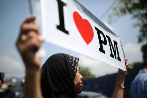 <p>A Barisan National party supporter displays a placard during a campaign rally in Kuala Lumpur on April 22, 2013. Malaysia is bracing for long-anticipated elections that have raised speculation of the country's first change of regime since independence from Britain in 1957.</p>