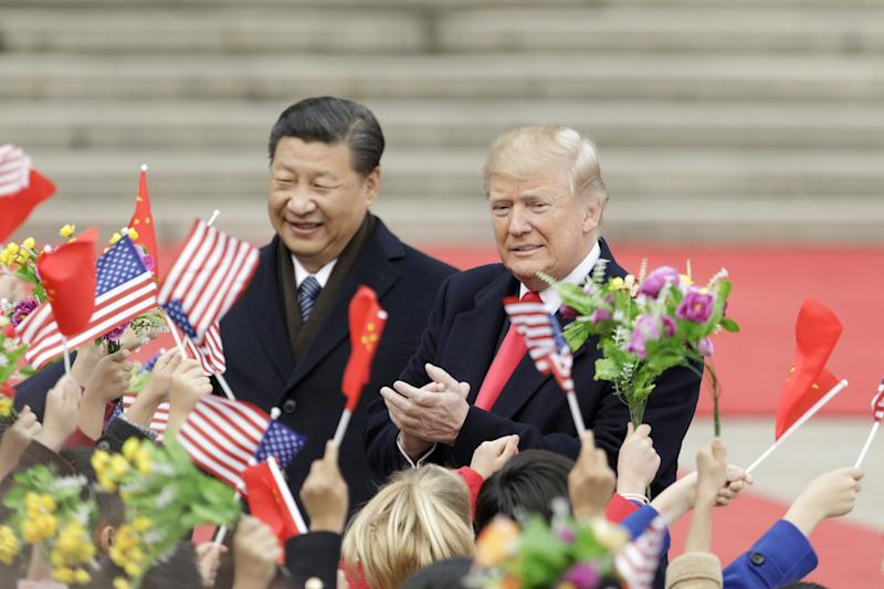 FILE: U.S. President Donald Trump, right, and Xi Jinping, China's president, greet attendees waving American and Chinese national flags during a welcome ceremony outside the Great Hall of the People in Beijing, China, on Thursday, Nov. 9, 2017. Sunday, January 20, 2019, marks the second anniversary of U.S. President Donald Trump's inauguration. Our editors select the best archive images looking back over Trumps second year in office. Photographer: Qilai Shen/Bloomberg via Getty Images