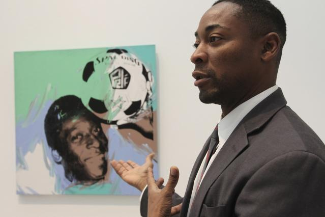 """Curator Franklin Sirmans stands next to """"Pele"""" by Andy Warhol during construction of the exhibition, """"Futbol: The Beautiful Game"""", at the Los Angeles County Museum of Art (LACMA) in Los Angeles, California, January 27, 2014. The exhibition reflects the global nature of the game, from paintings by an artist obsessed by English club Manchester United to a Colombian artist who shoots a video of a pick-up game in a small courtyard to a photograph of North African slippers bearing a Nike-like swoosh. """"Futbol: The Beautiful Game"""" opens February 2 and ends July 20, one week after the world crowns its new champion in the Maracana. Picture taken January 27, 2014. To match Feature SOCCER-WORLDCUP/ART REUTERS/David McNew (UNITED STATES - Tags: SOCIETY SPORT SOCCER WORLD CUP)"""