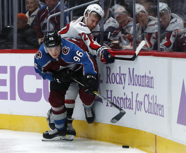 Colorado Avalanche right wing Mikko Rantanen, front, and Washington Capitals center Travis Boyd work for the puck along the boards during the third period of an NHL hockey game Friday, Nov. 16, 2018, in Denver. The Capitals won 3-2 in overtime. (AP Photo/David Zalubowski)