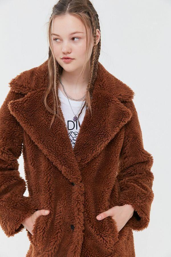 "This mid-length brown teddy coat has a button-front closure topped with oversized, notched lapels and pockets at the waist. <strong><a href=""https://fave.co/2HYN8H4"" target=""_blank"" rel=""noopener noreferrer"">Find it for $149 at Urban Outfitters</a></strong>."