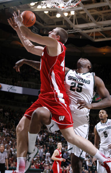 Wisconsin's Jared Berggren, left, is fouled by Michigan State's Derrick Nix (25) as he attempts a shot during the first half of an NCAA college basketball game, Thursday, March 7, 2013, in East Lansing, Mich. (AP Photo/Al Goldis)