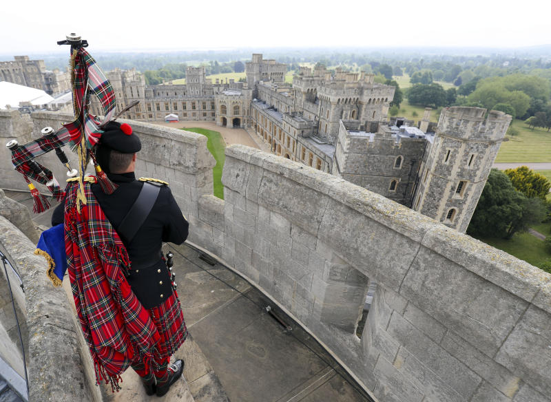 """Her Majesty The Queen's Piper, Pipe Major Richard Grisdale, of The Royal Regiment of Scotland, on top of the Round Tower at Windsor Castle, joining pipers and musicians in marking the Battle of St Valery-en-Caux, where he played the pipers' march Heroes of St Valery to commemorate the thousands of Scots who were killed or captured during """"the forgotten Dunkirk"""" 80 years ago."""