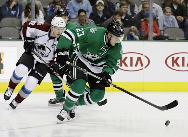 Dallas Stars defenseman Kevin Connauton (23) handles the puck as Colorado Avalanche's Gabriel Landeskog (92), of Sweden, trails in the second period of an NHL hockey game, Tuesday, Dec. 17, 2013, in Dallas. (AP Photo/Tony Gutierrez)