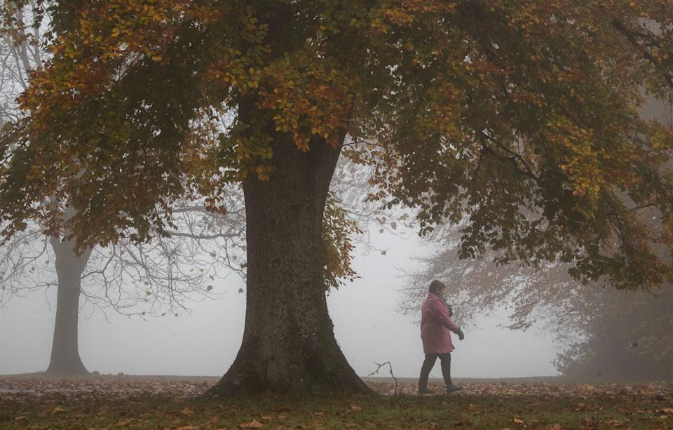 A lady walks through the fog in the War Memorial Park in Basingstoke, Hampshire.