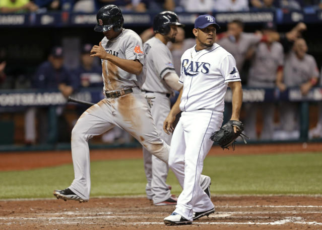 Tampa Bay Rays pitcher Joel Peralta, right, looks back as Boston Red Sox's Xander Bogaerts scores on a wild pitch by Peralta in the seventh inning in Game 4 of an American League baseball division series, Tuesday, Oct. 8, 2013, in St. Petersburg, Fla. (AP Photo/Chris O'Meara)