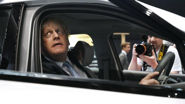 Britain's Prime Minister Boris Johnson sits inside a hydrogen-powered car as he visits the stalls on the third day of the annual Conservative Party Conference at the Manchester Central convention centre in Manchester (Photo: PAUL ELLIS via Getty Images)