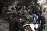 Afghan security personnel and people remove a damaged vehicle from the site of a bomb attack in Kabul, Afghanistan, Saturday, Feb. 20, 2021. Three separate explosions in the capital Kabul on Saturday killed and wounded numerous people an Afghan official said. (AP Photo/Rahmat Gul)