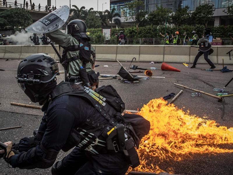 Riot police react after one of the protesters thrown a bottle with flammable liquid during an anti-government march in Kwun Tong, Hong Kong: EPA