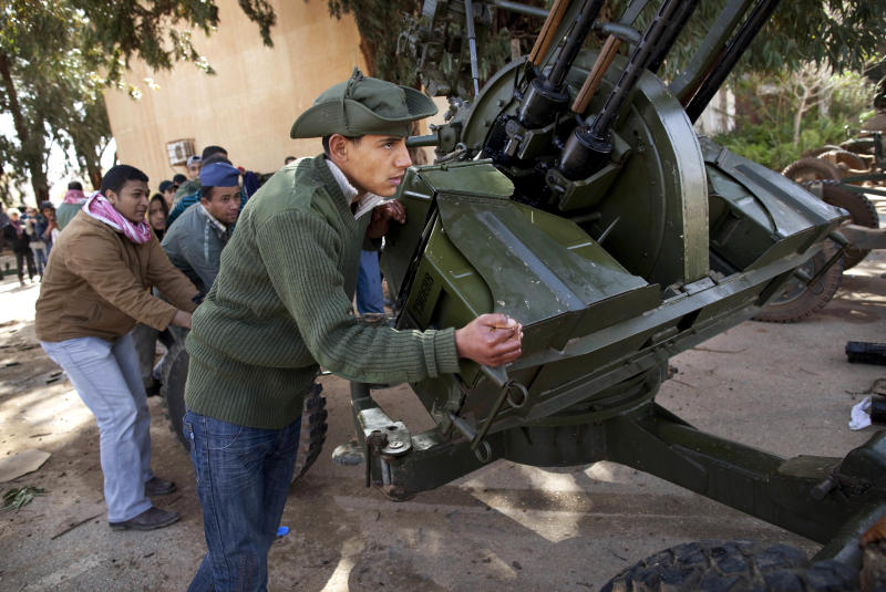 New Libyan rebel recruits from the forces against Libyan leader Moammar Gadhafi  push an anti-aircraft gun at a military base in Benghazi, eastern Libya, Tuesday, March 1 , 2011. (AP Photo/Kevin Frayer)