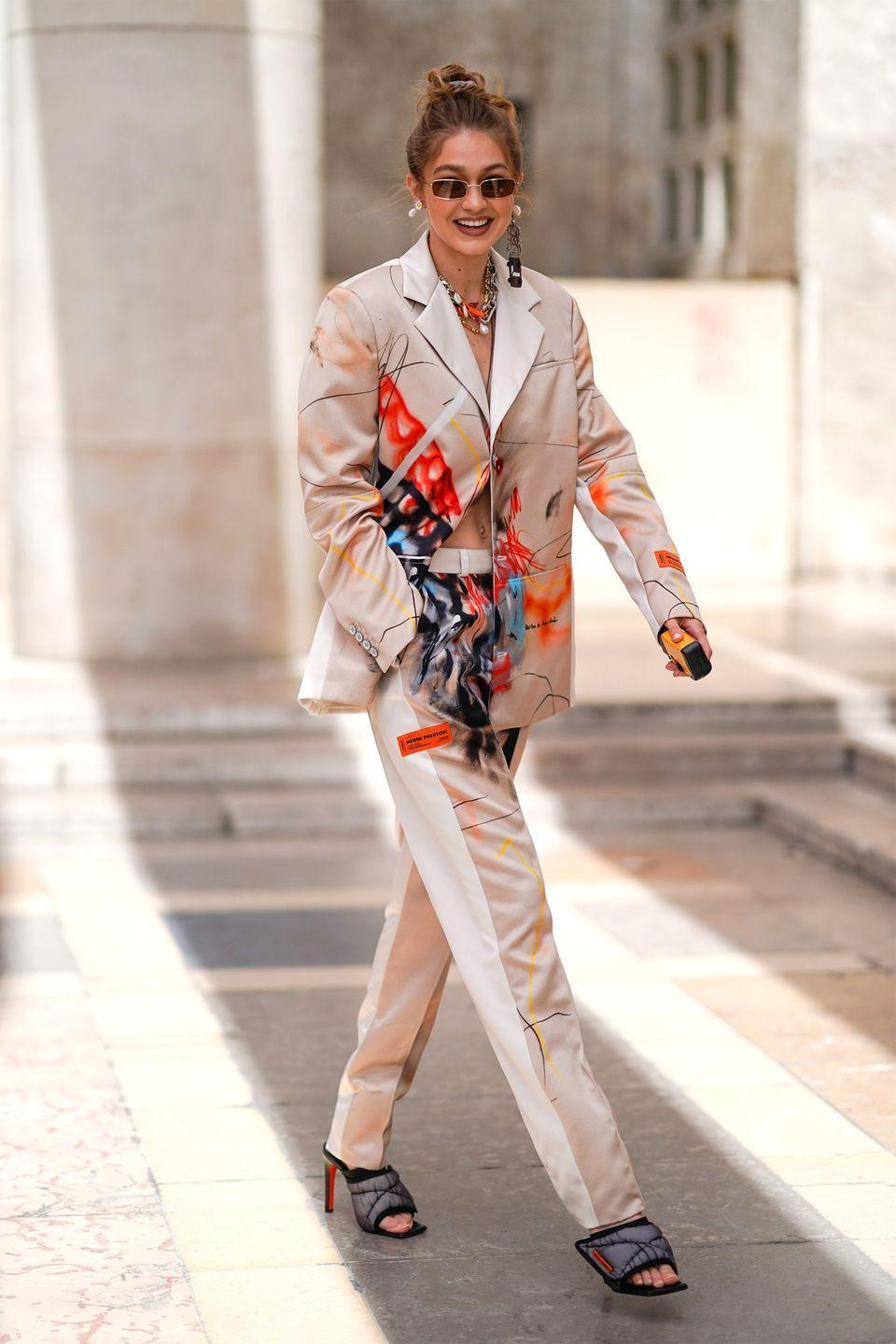 <p>In an artfully patterned pantsuit, layered necklaces, and quilted charcoal gray heels.</p>