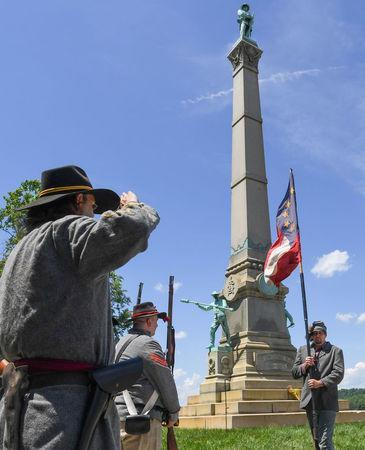 A color guard, dressed in Confederate soldier uniform, salutes the official flag of the Confederacy during a dedication ceremony in Brandenburg, Kentucky, U.S. May 29, 2017 for a Civil War Confederate Soldier Memorial recently removed from the campus of the University of Louisville. REUTERS/Bryan Woolston