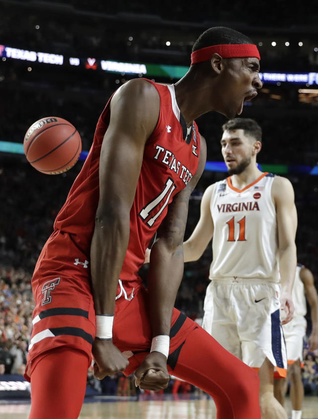 Texas Tech forward Tariq Owens celebrates in front of Virginia guard Ty Jerome, right, after dunking the ball during the first half in the championship game of the Final Four NCAA college basketball tournament, Monday, April 8, 2019, in Minneapolis. (AP Photo/David J. Phillip)