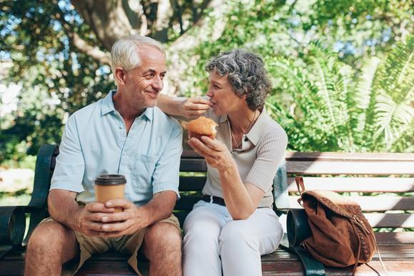 Senior couple on a park bench, with the male holding a cup of coffee and the female eating a muffin
