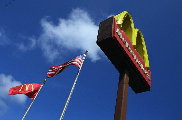 A sign for a McDonald's restaurant in front of an American flag on July 23, 2012 in Miami, Florida. Thousands of workers at McDonald's and other fast food outlets across the United States went on strike Thursday in a growing movement for higher wages in the industry