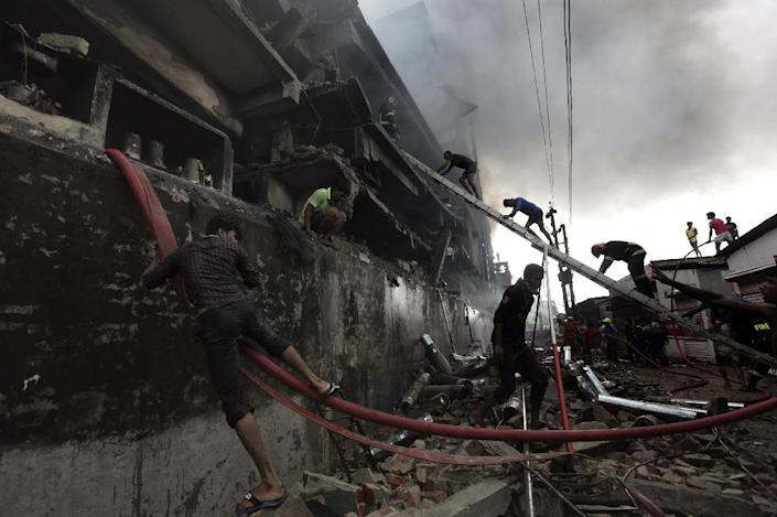 Bangladeshi firefighters and volunteers work to put out a fire and search for survivors at the site of an explosion in a factory in Tongi, on September 10, 2016 (AFP Photo/Rajib Dhar)