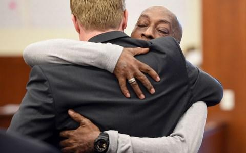DeWayne Johnson hugs one of his lawyers after hearing the verdict  - Credit: JOSH EDELSON/AFP