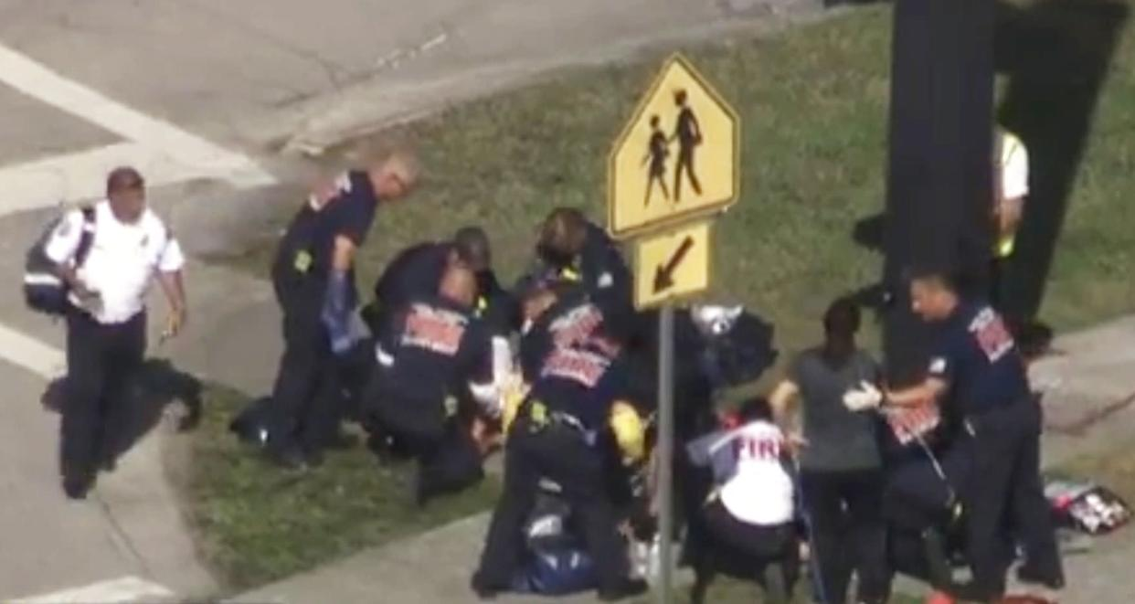 Rescue workers help a victim near Marjory Stoneman Douglas High School.
