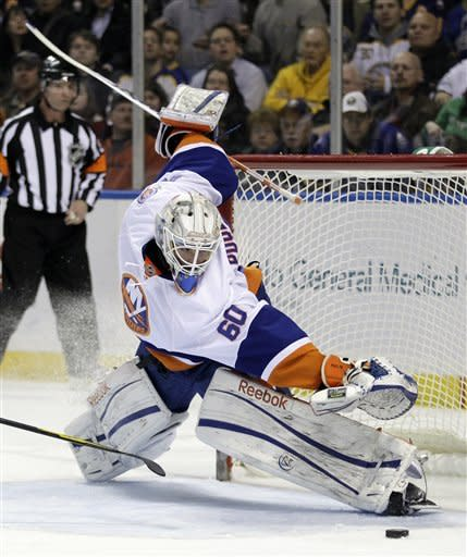New York Islanders goalie Kevin Poulin makes a save on a shot by Buffalo Sabres' Matt Ellis, not shown, during the first period of an NHL hockey game in Buffalo, N.Y., Tuesday, Feb. 21, 2012. (AP Photo/David Duprey)