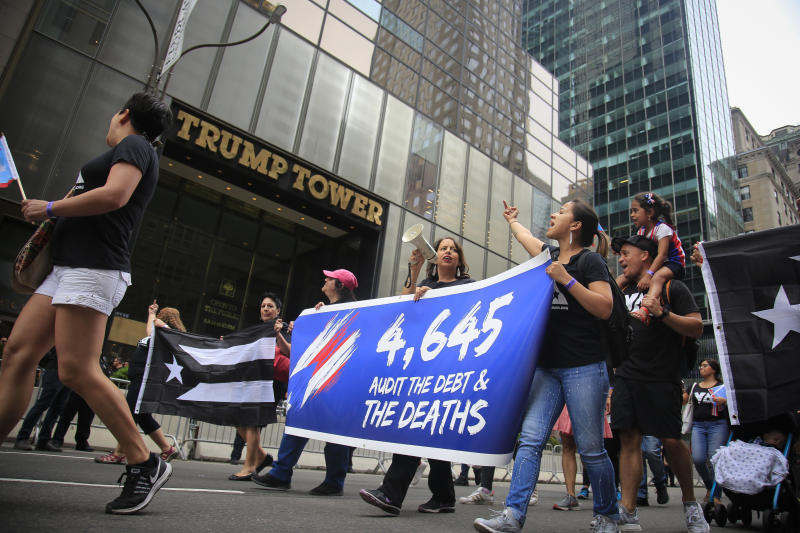 "Puerto Rico Day Parade participants in 2018 turn their attention to Trump Tower as they march behind a banner in protest, marking ""4,645"" deaths in the aftermath of hurricane Maria on the island and the Trump's administration emergency response. (Photo: Bebeto Matthews/AP)"